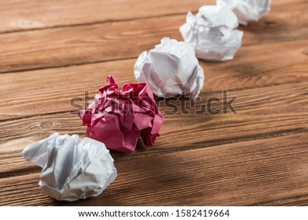 White crumpled up piece of paper on wooden table as idea #1582419664