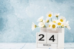 White cube calendar for march decorated with daisy flowers over blue background with copy space