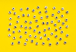 White cubes with letters scattered randomly on a yellow background. The Image can be used for many purposes, book covers or concepts relating to grammar and typography.