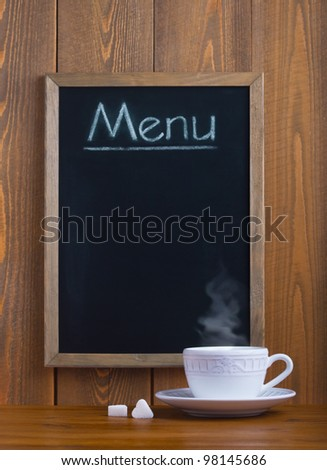 White cup and chalk board with the menu
