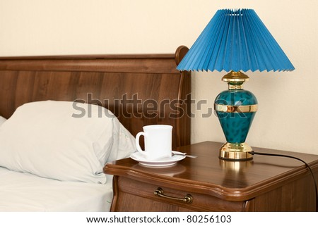 White cup and lamp on a bedside nightstand in the bedroom