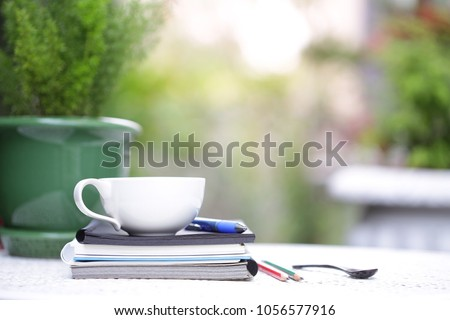 White cup and notebooks with green plant at outdoor