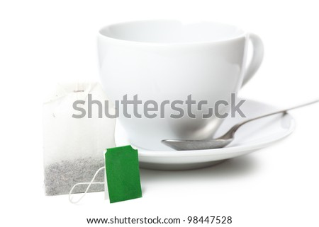 White cup and white saucer with teabag over white background