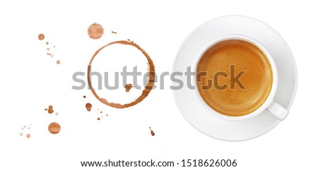White cup full of espresso coffee on saucer, with brown circle coffee stains and drops isolated on white background, elevated top view, directly above