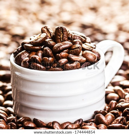 White Cup full of roasted coffee beans on heap of coffee beans background. Coffee background texture with copy space for text, close up.