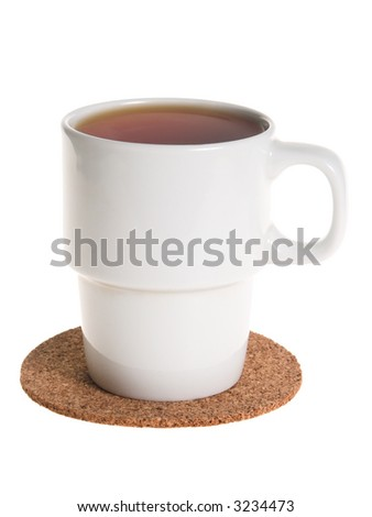 White cup full of tea on a cork pad taken from side isolated on white
