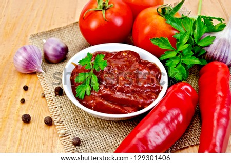 White cup ketchup, tomatoes, two red fresh chilli peppers, garlic, peppercorns, mustard, parsley against burlap cloth and wooden board