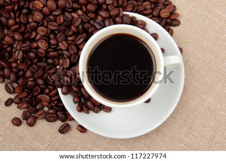 White cup of aroma coffee with dark brown coffee beans over cloth sack
