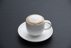 White cup of cappuccino on a black textured stone slab, side view. White foam.