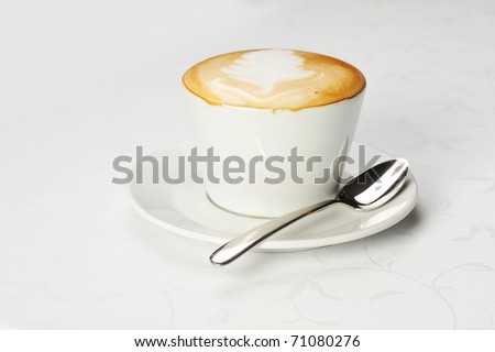 White cup of cappuccino with brown and white foam on top. Object  on white