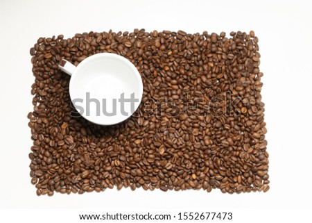 White cup of coffe in coffee beans. Coffee beans the shape of rectangle on the white backround. Separate coffee beans. Food and drink background or texture.