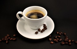White cup of coffee a dark background stock images. Cup of coffee on a black background. Cup of coffee with coffee beans stock images