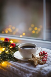 White cup of coffee and Christmas gingerbread near fir wreath decorated with red balls, burning candle and coiled with glowing garland with warm light near window. New Year evening at home.