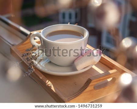 White cup of coffee is situated on the wooden tray at the windowsill in the rays of morning sun, there are pale rose marshmallow and lavender flowers on the plate.