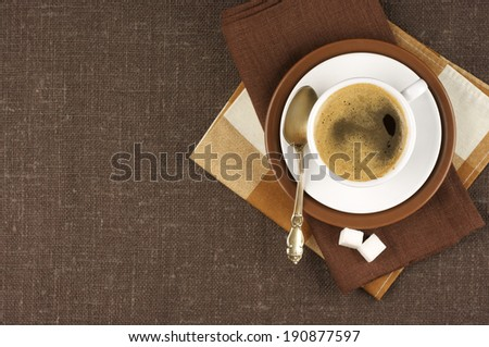 White cup of coffee on brown linen. Top view.