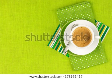 White cup of coffee on green linen. Top view.