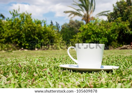 White cup of coffee on landscape background. Profile view.