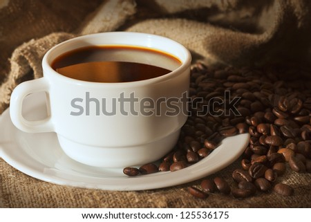 White cup of coffee on sacking and coffee beans still life