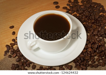 White cup of coffee with a lot of coffee beans on the table