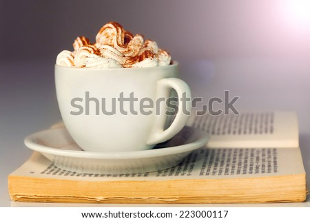 White cup of coffee with cream, on the open book.