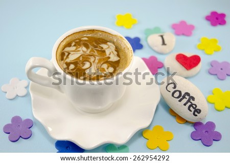 White cup of coffee with decorated foam and rocks saying \
