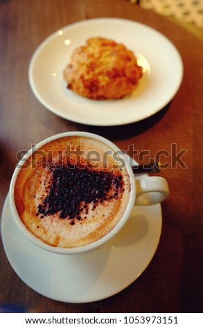 White cup of coffee with scone on a wooden table. instagram style toned image for good morning quotes