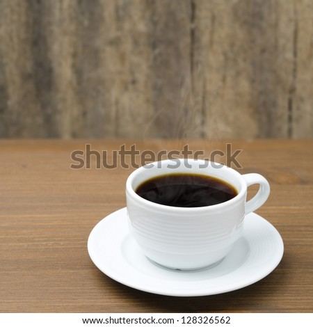white cup of coffee with steam on a wooden table