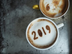 White cup of coffee with the number 2019 on frothy surface with yellow cup of cappuccino on grey cement background. Food art creative concept for active days in New Year 2019. (space for text)