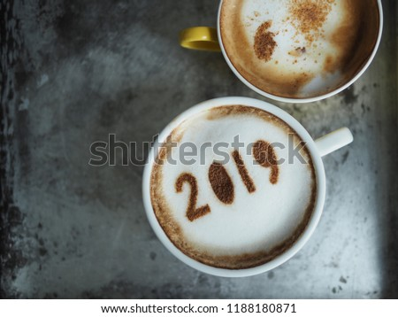 White cup of coffee with the number 2019 on frothy surface with yellow cup of cappuccino on grey cement background. Food art creative concept for active days in New Year 2019. (space for text) #1188180871