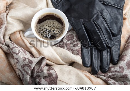 White cup of espresso in the folds of the women's shawls and black leather gloves