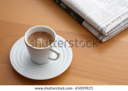 white cup of Espresso with newspaper on a table in a cafe