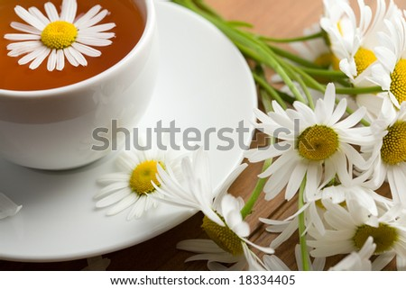 white cup of herbal tea and camomile flowers