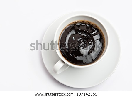 White cup of hot bracing coffee. Beverage is shaking and full of energy