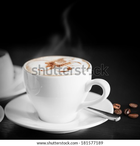 White cup of hot cappuccino on black background