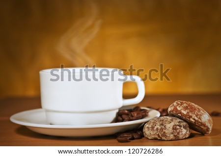 White cup of hot coffee on a saucer with steam and two cakes