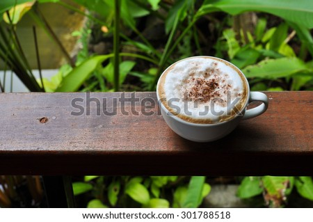 white cup of hot coffee on natural green background