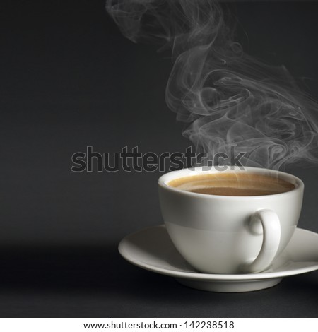 White cup of hot coffee with steam on dark gray background.
