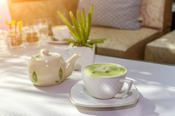 White cup of matcha tea or green tea on wooden table after drink in the morning at the matcha green tea shop