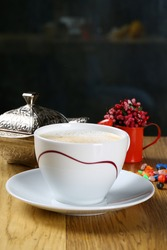 White cup of milky coffee on table
