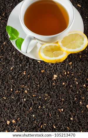 White cup of tea on dried tea background