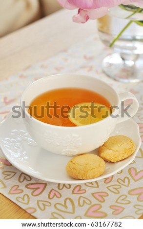 White cup of tea with lemon and amaretti cookies