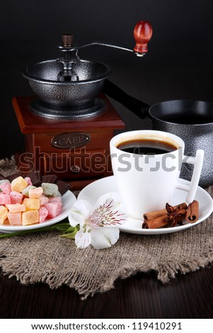 White cup of Turkish coffee with rahat delight, coffee pot and coffee mill on wooden table