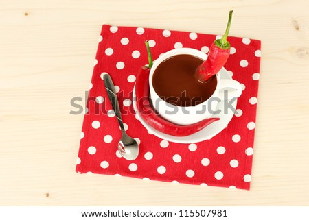 white cup with hot chocolate and chili pepper on wooden background