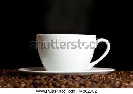 White cup with hot coffee and steam on dark background
