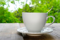 white cup with hot fragrant coffee, tea, cappuccino on a light wooden table against a green summer garden, concept of outdoor tea drinking, good weather, coffee break