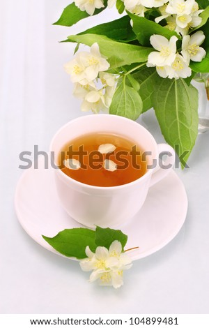 White cup with jasmine tea and flowers