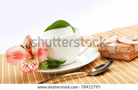 najromanticnija soljica za kafu...caj - Page 5 Stock-photo-white-cup-with-pink-flowers-and-small-gifts-on-a-light-table-78412795