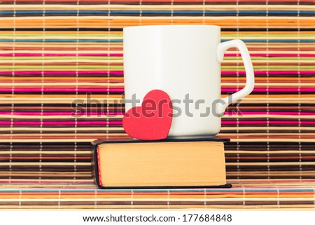 White cup with red heart stand on the book on a color background from bamboo sticks