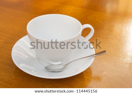 white cup with spoon and saucer on wooden table