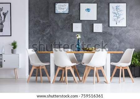 White cupboard and wooden table in monochromatic dining room with gallery on wall #759516361